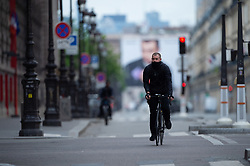 Cyclist wearing facemask ride bike on Rivoli Street in Paris on May 4, 2020, on the forty-ninth day of a strict lockdown in France, in place to attempt to stop the spread of the new coronavirus (COVID-19). Photo by Raphael Lafargue/ABACAPRESS.COM