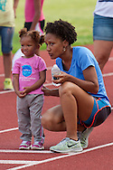 Middletown, New York - A woman talks to a young girl getting ready to compete in the long jummp during the Twilight Track and Field Series run by the Middletown High School Varsity track program on July 22, 2014.