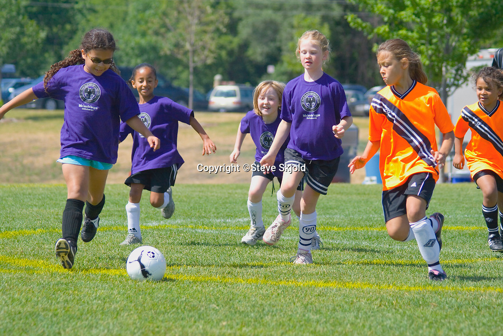 Girls age 10 kicking ball in soccer game. St Paul Minnesota MN USA