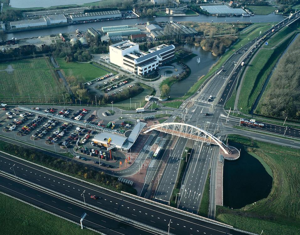 Nederland, Zuid-Holland, Leiden, 01-12-2005;  Transferium 't Schouw, mogelijkheden tot parkeren en over te stappen op de bus te stappen richting Den Haag of Leiden; gelegen aan de westrand van Leiden, op de grens met de binnenstad en op de kruising van autosnelweg  A44 (richting Wassenaar) met de lokale weg N206 (richting Rijnsburg en Katwijk); naast het transferium een vestiging ('restaurant') van de onvermijdelijk fastfood keten McDonald's; het witte bedrijfsgebouw is van multinational Nalco (waterzuivering, waterbehandeling), het water daarachter is van de gekanaliseerde rivier de Rijn (lokaal ook: Oude Rijn); transferia, overstappen, file, bereikbaarheid, forensen, automobiliteit, automobilist; fast food, hamburger, MacDonald, voeding.<br /> luchtfoto (toeslag), aerial photo (additional fee)<br /> foto /photo Siebe Swart