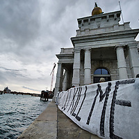 VENICE, ITALY - DECEMBER 18: Protesters at Punta della Salute hold a banner as they protest against large cruise ships in St Mark's basin on December 18, 2011 in Venice, Italy. Venetians and Environmentalists are opposed tocruise ships, which plough through the shallow Venetian lagoon, damaging the fragile buildings and canal banks. (Photo by Marco Secchi/Getty Images)