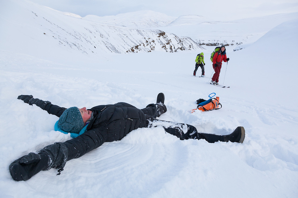 Kiya Riverman makes a snow angel as Michelle Blade (front) and Nate Stevens ski past in Foxdalen, Svalbard.