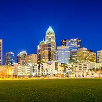 Charlotte skyline at night panorama photo with Romare Bearden Park and downtown Charlotte buildings against a blue sky. Charlotte is a major city in North Carolina in the Eastern United States.