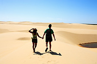 couple walking hand in hand on the desert sand dunes of the Lencois Maranheses National Park