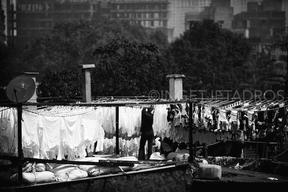 A laundryman hangs washed clothes to dry at the Dhobi Ghat open air laundry in Mumbai. Exclusive at Getty Images<br /> http://www.gettyimages.com.au/Search/Search.aspx?contractUrl=2&amp;language=en-US&amp;assetType=image&amp;p=ingetje+tadros#2
