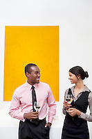 Two young executives in front of yellow painting