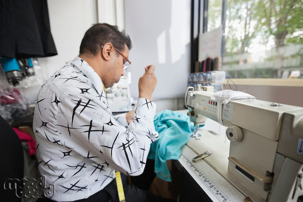 Side view of male tailor stitching cloth while sitting at sewing machine