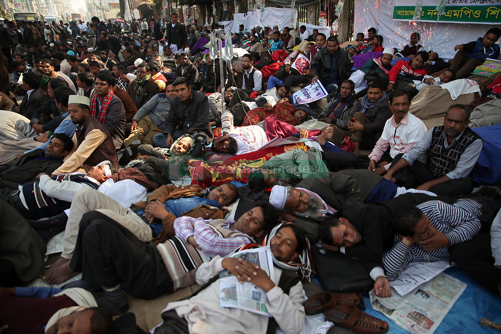 January 3, 2018 - Dhaka, Bangladesh - Non-MPO (monthly pay order) teachers from different non-government institutions, lay down in the street as they continue the four day of their fast unto death hunger strike program in front of the National Press Club in Dhaka, Bangladesh, 03 January 2018. Some hundred teachers went for hunger strike demanding their inclusion of the government-approved educational MPO facilities while more than 80,000 teachers from 5,242 non-MPO institutions are working without any pay, according to the leaders. (Credit Image: © Monirul Alam/NurPhoto via ZUMA Press)
