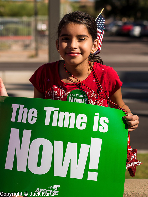 05 OCTOBER 2013 - PHOENIX, ARIZONA:     A child finishes a frozen snack before participating in an immigration march through downtown Phoenix Saturday to demonstrate for the DREAM Act and immigration reform. It was a part of the National Day of Dignity and Respect organized by the Action Network.    PHOTO BY JACK KURTZ