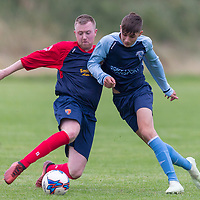 Shannon Town's Kai Khetan is pushed off the ball by Shannon Olympic's Ray Quigley Ryan Kelly