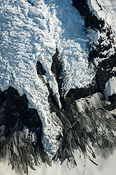 Fallen debris on the side of a valley of the Johns Hopkins Glacier in Glacier Bay National Park and Preserve appears to be almost feather-like.<br /> <br /> Glacier Bay National Park is located in southeast Alaska. Known for its spectacular tidewater glaciers, icefields, and tall costal mountains, the park is also an important marine wilderness area. The park a popular destination for cruise ships, is also known for its sea kayaking and wildlife viewing opportunities. <br /> <br /> Glacier Bay National Park is home to humpback whales which feed in the park's protected waters during the summer, both black and grizzly bears, moose, wolves, sea otters, harbor seals, steller's sea lions and numerous species of sea birds. <br /> <br /> The dynamically changing park, known for its large, contiguous, intact ecosystems, is a United Nations biosphere reserve and a UNESCO World Heritage site.