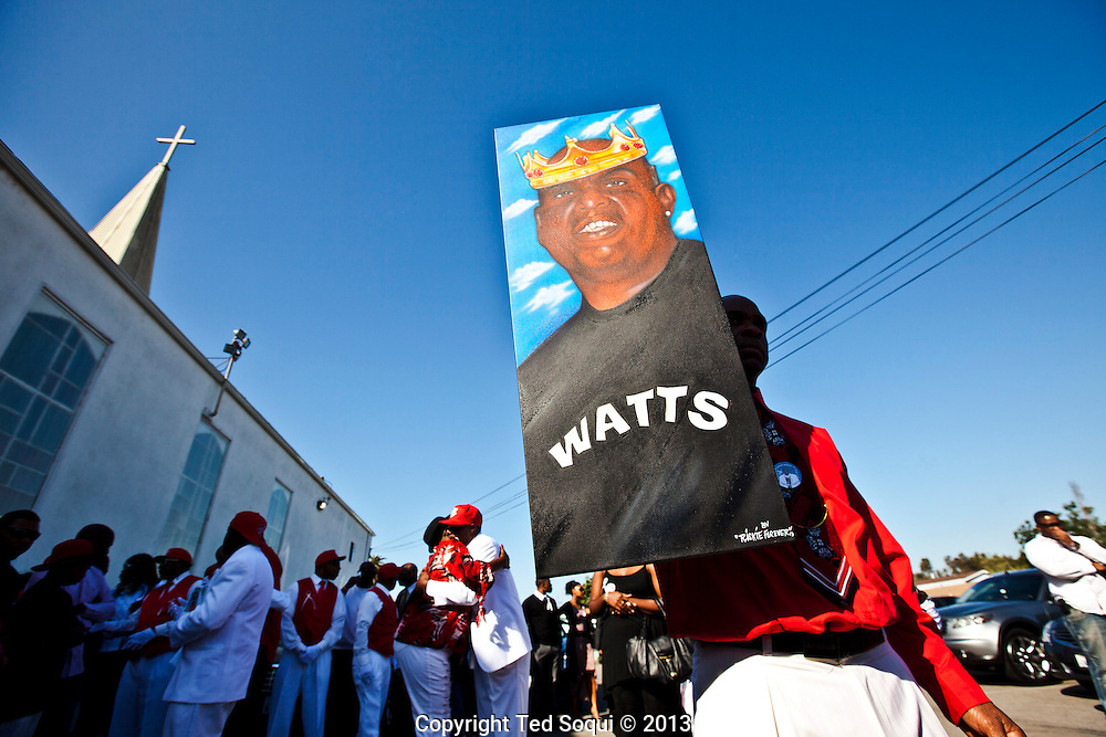 A man carries a painting of Kevin.<br /> Funeral services for Kevin &quot;Flipside&quot; White at Macedonia Church in Watts.<br /> White was shot dead in what is believed to be an unprovoked attack during a gang conflict at Watts' Nickerson Gardens and Jordan Downs housing projects.<br /> Flipside, 44, was a founding member of Watts' first major label hip hop act, O.F.T.B. (Operation From The Bottom).
