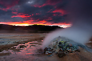 The plains of Hverir full of  fumaroles and bubbling mudpots are transformed in a hellish landscape by the red light of the setting sun