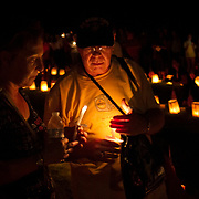 Sally Calderone and husband, Thomas Mahan light candles at the Soldiers National Cemetery, during the Sesquicentennial Anniversary of the Battle of Gettysburg, Pennsylvania on Sunday, June 30, 2013.  Thousands of flags were planted and candles lit as part of the Memorial Luminaria program at the cemetery.