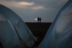 A Syrian couple with their son walks at sunset thought Atmah's refugee camp. Idlib province, Syria. Situated along the Turkish border Atmah's refugee camp is considered the biggest refugee camp inside Syria's territory with an estimated number of 13,000 refugees and growing by the day. Is the biggest in an area with another two camps.,000 refugees and growing by the day. Is the biggest in an area with another two camps, Syria, February 4, 2013. Photo by Daniel Leal-Olivas / i-Images.
