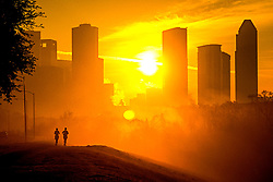 Sunrise with two joggers along Buffalo Bayou Hike and Bike trail in front of the Houston, Texas skyline.