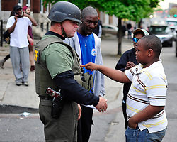 A young boy jokingly pokes the armor protective gear of a Maryland Sheriff who he knows from a youth program for inner city children on May 1, 2015, in Baltimore, Md.