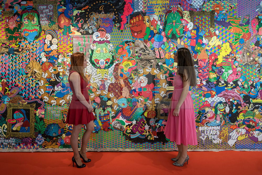 """© Licensed to London News Pictures. 04/10/2018. LONDON, UK. Staff members pose next to """"Speculative Entertainment No 1, London Edition"""" by Uji Hahan Handoko Eko Saputro. Preview of Moniker Art Fair, taking place during Frieze Week at the Old Truman Brewery, near Brick Lane.  Now in its tenth year, the fair embraces contemporary urban art from emerging and established artists  This year, the show's theme is 'Uncensored', shedding light on social, economic and ecological issues, and is open 4 to 7 October.  Photo credit: Stephen Chung/LNP"""