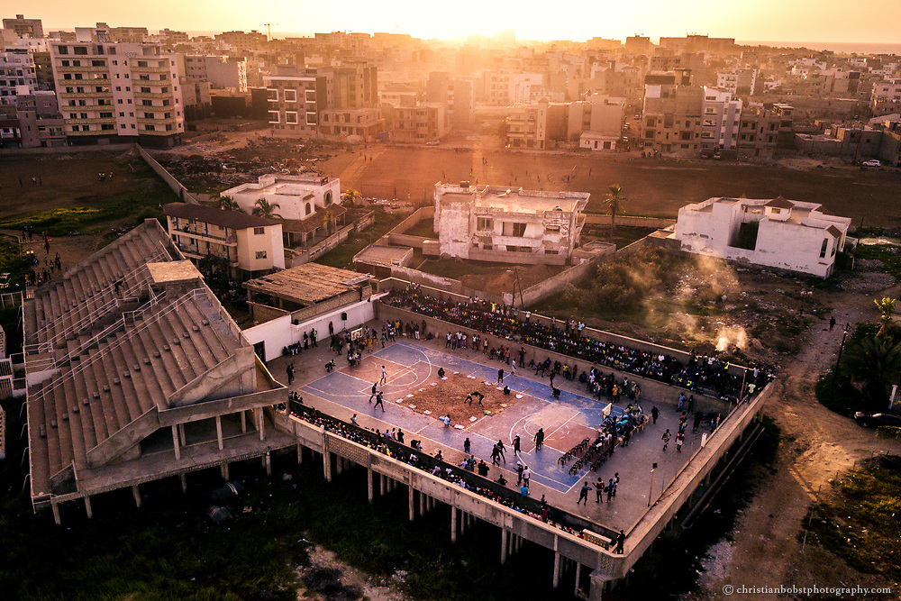 """November 4, 2017. At the """"Olympique de Ngor"""" stadium, a local wrestling tournament is held on the basketball court, with Kherou Ngor also taking part to support the wrestlers in his neighbourhood. Kherou, who has already won big competitions in the biggest stadium of Dakar in front of tens of thousands of spectators, has many loyal fans and thus guarantees the organizers of wrestling matches a good number of spectators, even at small wrestling events."""