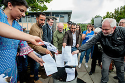Pictured: Protesters including speakers Aamer Anwar and Dennis Canavan burn the eviction letters from private firm SERCO.<br /> <br /> Protesters gathered outside the main Home Office building in Glasgow to protest at private company SERCO's attempts to evict failed asylum seekers from their homes.<br /> <br /> © Dave Johnston / EEm