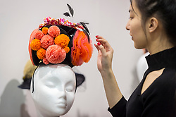 """© Licensed to London News Pictures. 05/04/2019. LONDON, UK. A gallery assistant checks a creation at """"The Great Hat Exhibition - World Garden"""", which is taking place at the Menier Gallery near London Bridge until 12 April 2019, as part of London Hat Week.  150 international milliners have created 200 hats inspired by the colours, flowers, plants and landscapes from around the world.  The exhibition is curated by Monique Lee Millinery and supported by X Terrace, a fashion platform.  Photo credit: Stephen Chung/LNP"""