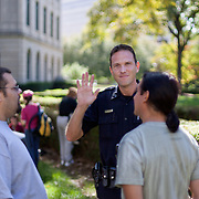 A CMPD officer waves as he chats with 2 protestors before a scheduled march to Bank of America HQ in uptown Charlotte.