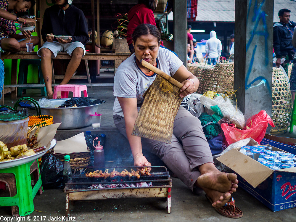 06 AUGUST 2017 - MENGWI, BALI, INDONESIA: A woman cooks sate (grilled meat) in the Bringkit Market, about 30 minutes from Denpasar. Bringkit Market is famous on Bali for its Sunday livestock and poultry market. Hundreds of the small Bali cows are bought and sold there every week. Bali's local markets are open on an every three day rotating schedule because venders travel from town to town. Before modern refrigeration and convenience stores became common place on Bali, markets were thriving community gatherings. Fewer people shop at markets now as more and more consumers go to convenience stores and more families have refrigerators.     PHOTO BY JACK KURTZ