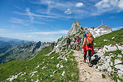 Hikers at Rotsteinpass (2120 m) in Switzerland, Europe. In the background, a transmission tower caps Säntis (2502 m), the highest mountain in the Alpstein massif of northeastern Switzerland, and highest of the Appenzell Alps. Appenzell Innerrhoden is Switzerland's most traditional and smallest-population canton (second smallest by area).