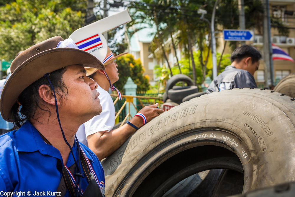 18 FEBRUARY 2014 - BANGKOK, THAILAND: Anti-government protestors in Bangkok take cover behind a tire barricade when police returned fire after somebody in the protestors fired towards police positions. Anti-government protestors aligned with Suthep Thaugsuban and the People's Democratic Reform Committee (PDRC) clashed with police Tuesday. Protestors opened fire on police with at rifles and handguns. Police returned fire with live ammunition and rubber bullets. The Bangkok Metropolitan Administration's Erawan Emergency Medical Centre reported that three civilians and a policeman were killed and 64 others were injured in the clashes between police and protesters.    PHOTO BY JACK KURTZ