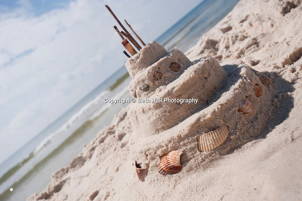 A sandcastle built to look like a birthday cake sits on the sandy beach in front of the ocean.