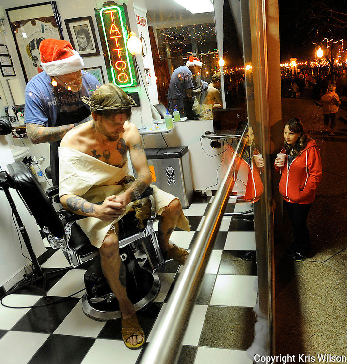 Kris Wilson/News Tribune.A passer by stops to watch as Capital Tattoo Co.'s J.R. Roberts puts fresh ink on a set of wings on the back of David Kroeger, who sits on display in the shop's window dressed as Jesus during the annual Living Windows event in downtown Jefferson City on Friday night.