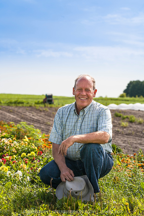 Ontario organic farmer, David Cohlmeyer, founder of  Cookstown Greens in a farm field under a blue sky.