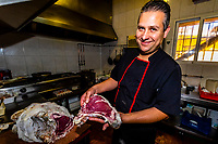 Chef Mario Perez cuts aged beef for a customer's meal, Restaurant La Tinaja, Guadix, Granada Province, Andalusia, Spain.