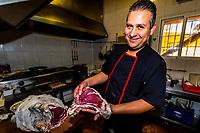 Chef Mario Perez cuts aged beef for a customer's meal, Restaurant La Tinaja, Guadix, Granada Province, Andalusia, Spain.