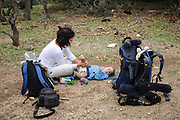 Mother hiker changes her two year baby boy's diaper outdoors