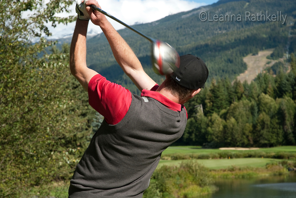 Golf Professional Dan Axford tees off the signature 16th hole at the Whistler Golf Course in Whistler, BC Canada.
