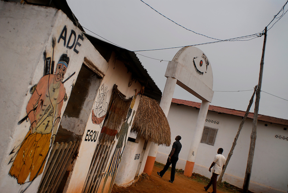 12-01-28  --  ANEHO, TOGO  -- An illegal fuel seller, at left, and a co-hort, at right, walk through a voodoo shrine the village of Glidji on January 28. The smugglers are often viewed as heroes as they provide jobs for the communities they operate in. Photo by Daniel Hayduk