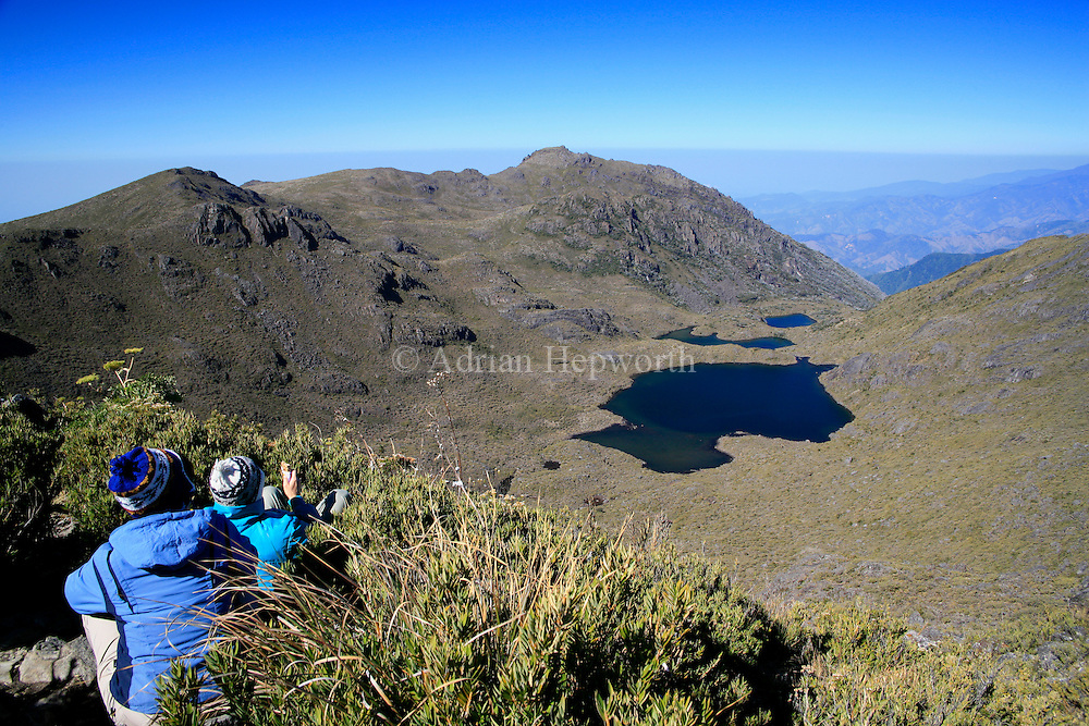 Tourists looking at Lake Chirripo from the summit of Mount Chirripo, Costa Rica's highest mountain (3820m). Chirripo National Park, Costa Rica.<br />