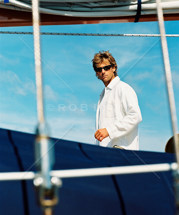Blond man wearing sunglasses looking through boat rigging