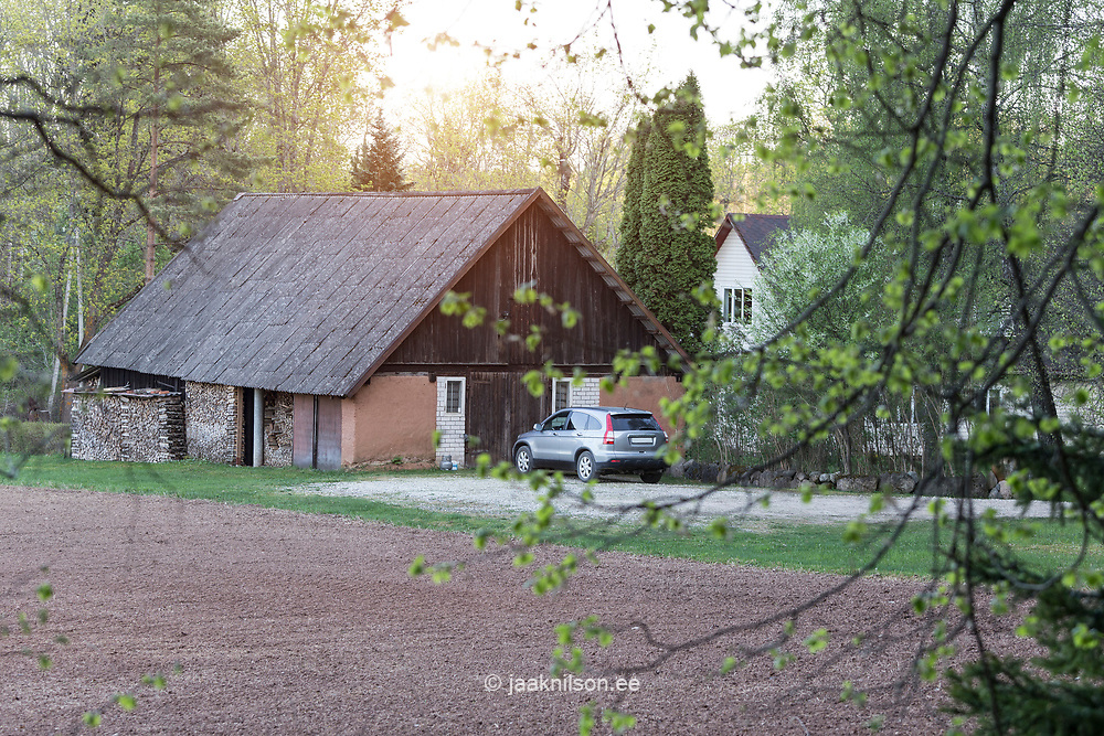 Vehicle parking by old shed in Estonia.Ariculture, field. Tree branches. Rural landscape.