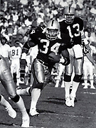 Los Angeles Raiders running back Bo Jackson (34) carries the ball after taking handoff from quarterback Jay Schroeder (13) against the Kansas City Chiefs, Sunday, Nov. 25, 1990, in Los Angeles. The Chiefs defeated the Raiders 27-24.