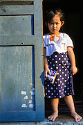 11 MARCH 2013 - LUANG PRABANG, LAOS:  A Lao girl stands in the doorway of her home in Luang Prabang. Luang Prabang has more than 30 temples and is a UNESCO World Heritage Site. It is the most visited tourist attraction in Laos.   PHOTO BY JACK KURTZ