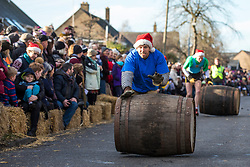 © Licensed to London News Pictures. 26/12/2017. Grantchester, UK. The annual Boxing Day barrel rolling relay race in Grantchester, Cambridgeshire. Four teams from local pubs compete to roll the empty barrels as rapidly as possible up and down the main road with the fastest time winning. Photo credit: Rob Pinney/LNP