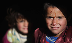 Afghan refugee children are seen under a tent at a refugee camp, Kabul, Afghanistan, January 2, 2013. Photo by Imago / i-Images...UK ONLY
