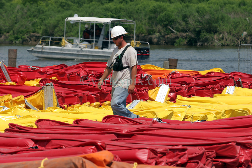 10 June 2010. Breton Sound Marina, Hopedale, Louisiana. USA.  <br /> Breton Sound Marina in Hopedale. Over 1,000 people now work in what was, just weeks ago empty fields. A city is rising out of the marshes to deal with BP's catastrophic oil spill in the Gulf of Mexico. Workers load and unload, repair and haul miles and miles of oil boom. The 'hard boom' is not owned by BP or the federal government. It is leased with prices allegedly over $1.00 a linear foot per day. In St Bernard Parish alone there is over 200,000 linear feet of hard boom. Someone, somewhere is making a fortune on the back of this crisis. Workers are hired by contractors, who themselves are hired by bigger contractors. Yet again, the middle men are making a fortune on the backs of workers and on the back of this crisis. The scandal continues to grow.<br /> The ecological and economic impact of BP's oil spill is devastating to the region. Oil from the Deepwater Horizon catastrophe is evading booms laid out to stop it thanks in part to the dispersants which means the oil travels at every depth of the Gulf and washes ashore wherever the current carries it. The Louisiana wetlands produce over 30% of America's seafood and oil and gas production. They are the most fertile wetlands and nurseries of their kind in the world. BP's oil is killing everything.<br /> Photo; Charlie Varley/varleypix.com
