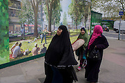 Muslim women carry heavy carpet past a regeneration project hoarding image at Elephant & Castle, London borough of Southwark.
