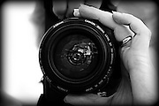 black & white image of photographer with canon 70-300 mm zoom lens in hand