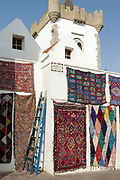Street Medina architecture, Asilah, Northern Morocco, 2015-08-03.<br /><br />Asilah is a sleepy fishing town in the North of Morocco, just one hour south of Tangier. While not completely off Morocco's well-beaten path, it's often missed by travellers bound inland for Fez or Chefchaouen, yet has a uniquely alluring charm. With an immaculately restored medina that's re-painted vivid shades of blue & white each summer, Asilah has the feel of being Morocco's own Santorini - a great spot to see the more chilled out, seaside town life in Morocco.  <br /><br />The town lies in the middle of a fascinating history in historical, architectural and artistic terms. It's 3,600 year old history that includes a varied range of occupiers, involving Roman, Arab Portuguese, Spanish and French colonisation. Many famous writers and artists have spent time here; in ancient times is it reported Herecules did a tour of the area and, more recently; Paul Bowles, Tennessee Williams, Edith Wharton, Jean Genet (who is buried in the nearby town of Larache), William Burroughs, Jimi Hendrix and Henri Matisse have all found the area inspiring. The Portuguese ramparts remain fully intact and a full day can be spent wandering through its old gates and the ever narrowing medina streets inside the walls.<br /><br />The architecture in Asilah has been heavily influenced by these different periods of occupation, which is one of the main reasons for its unique and characterful feel. Evidence of Mediterranean design can be seen in the rampart walls and gates themselves, reflecting the Spanish & Portuguese influence on the Asilah's development, Roman ruins can be found in the nearby town of Larache and Arab influences are more subtly found in the decorative window shutters and the labyrinth like medina layout to the streets. <br /><br />If a lover of the quirkier details found in the medinas of Morocco, then Asilah won't disappoint, with hundreds of creatively designed doorways, decorative window shutters 