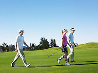 Three young golfers on course