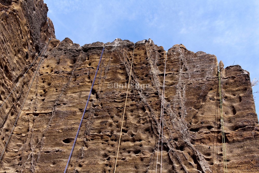 climbing ropes hanging from the top of a rock mountain Japan